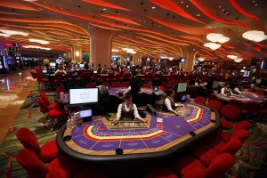 In this Sept. 20, 2012 photo, Croupiers sit at a baccarat gaming table inside a casino during the opening day of Sheraton Macao Hotel at the Sands Cotai Central in Macau. Macau is in the midst of one of the greatest gambling booms the world has ever known. To rival it, Las Vegas would have to attract six times as many visitors  essentially every man, woman and child in America. Wynn Las Vegas now makes nearly three-quarters of its profits in Macau. Sands, which owns the Venetian and Palazzo, earns two-thirds of its revenue there. (AP Photo/Kin Cheung)